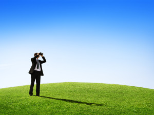 Business man observing nature with a telescope outdoors.