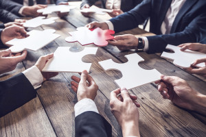 Business people and puzzle on wooden table, teamwork concept